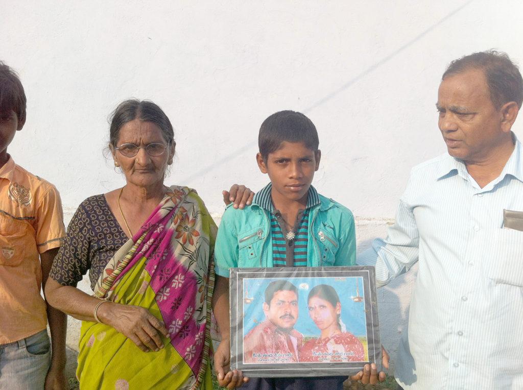 Indischer Waisenjunge aus einer Kleinbauernfamilie mit dem Foto seiner verstorbenen Eltern