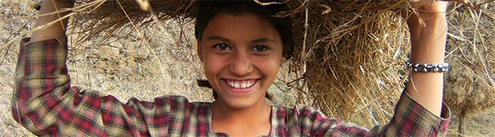 Indisches Mädchen bei der Feldarbeit, glücklich mit natürlicher nachhaltiger Landwirtschaft